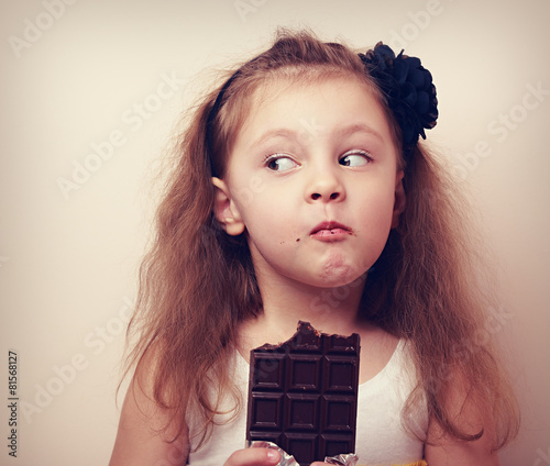 Leinwanddruck Bild Thinking humor kid face eating chocolate. Closeup vintage