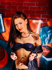 Woman with body art aganist graffiti brick wall.