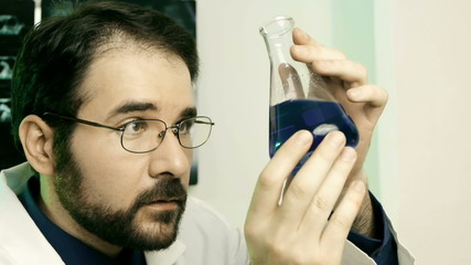 Male Scientist Looking at Flask