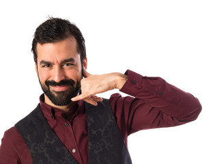 Man wearing waistcoat making phone gesture