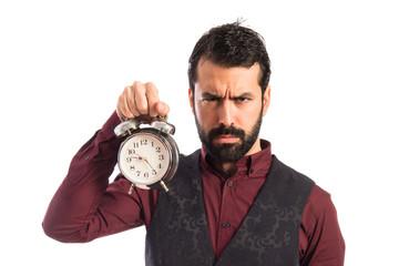 Angry man wearing waistcoat holding vintage clock