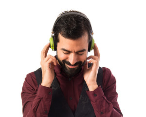 Man wearing waistcoat listening music