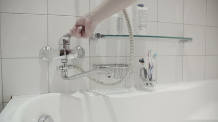 the man opens  tap in white bathroom slow motion
