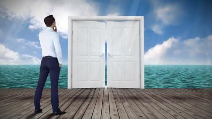 Door opening to ocean watched by businessman