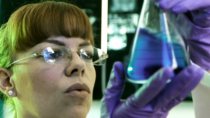 Female Scientist Looking at Flask