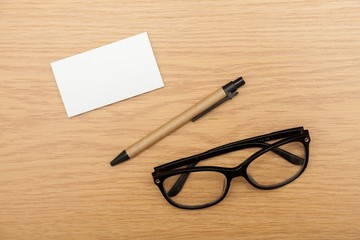 Glasses. Blank business cards with pen and glasses on wooden