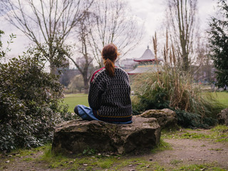 Young woman sitting on a rock in the park