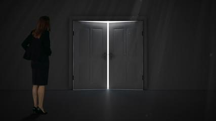Businesswoman watching door open to light