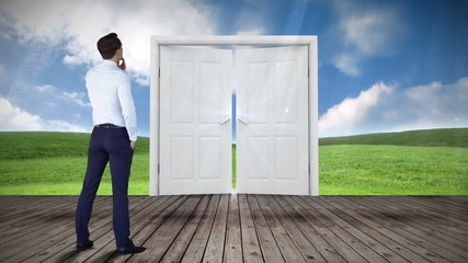 Door opening to green meadow watched by businessman
