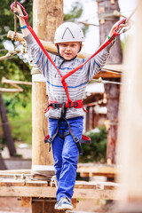 Little boy in safe equipment on rope track