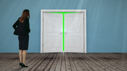 Door opening to green screen watched by businesswoman