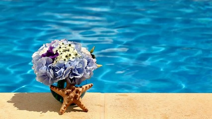 Concept background summer pool, flowers and a starfish shell