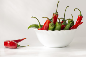 Red and green hot chili pepper in a ceramic bowl isolated