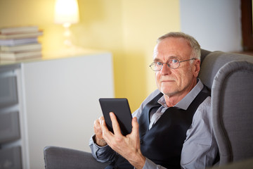 Senior man at home reading on a e-book 6
