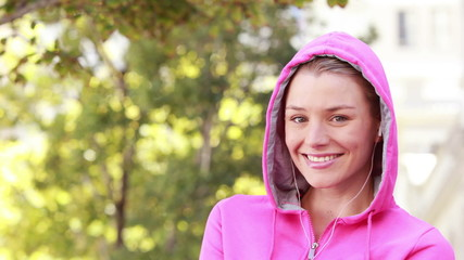 Pretty jogger putting music on her smartphone