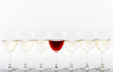 Red wine among white wine glasses Individuality concept
