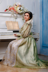 queen in royal dress near the piano