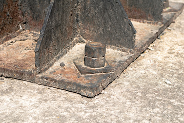 old iron construction bolted standing on concrete