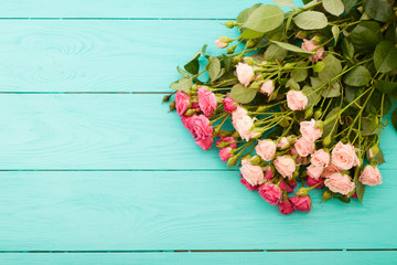 Pink and beige roses on blue wooden background.