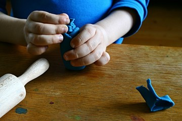 5 years old boy hands modelling object from blue plasticine