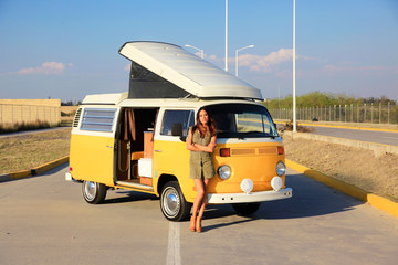 Beautiful woman standing in front of a yellow camper