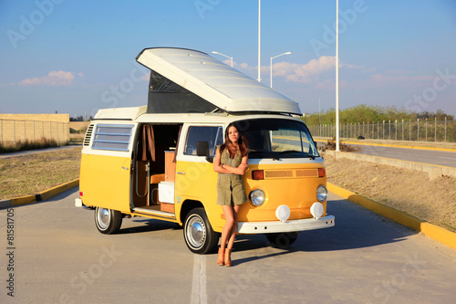 Beautiful woman standing in front of a yellow camper - 81581705