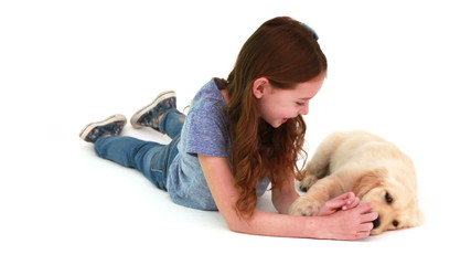 Smiling girl playing with cute puppy