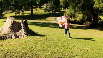 Happy little girl holding balloons