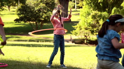 Little friends playing with hula hoops in park