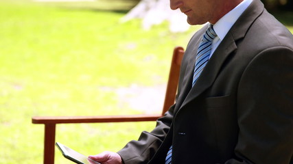 Businessman using tablet in the park