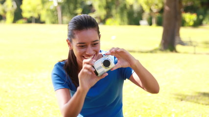 Smiling brunette taking pictures in the park