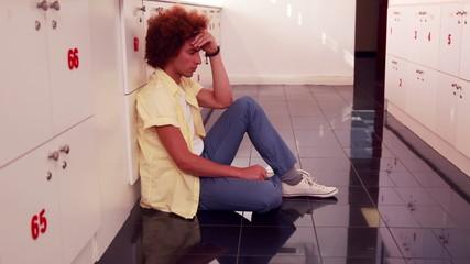 Depressed student sitting on the floor
