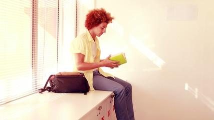 Happy student sitting on lockers