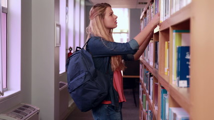 Pretty blonde student taking book from shelf