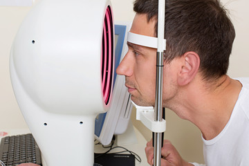 Man having his eyes examined by an eye elderly doctor.