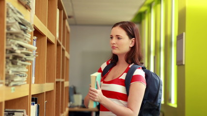 Pretty student taking book from shelf