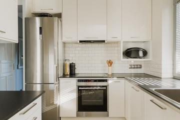 Chrome fridge in white kitchen