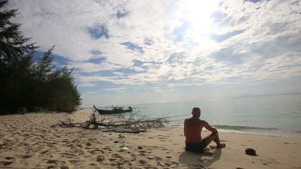 buddha monk sits on beach with rosary at island