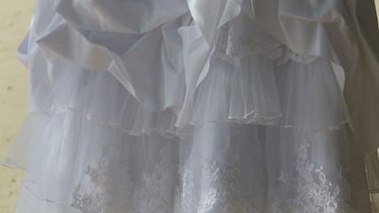 white wedding dress hangs on green tree