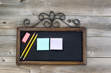 Antique chalkboard with supplies on rustic wood
