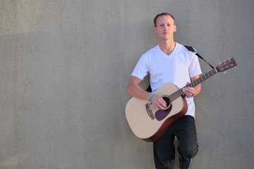 Young man leaning against wall playing acoustic guitar