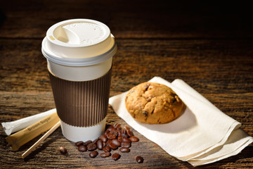 Paper cup of coffee and cookie on wooden background