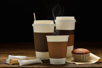Paper cups of coffee with smoke and cake on wooden background