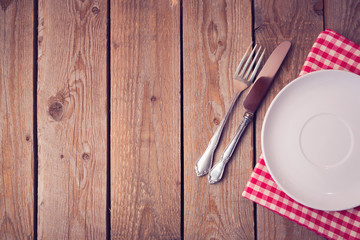 Background with empty plate on wooden table. View from above