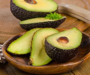 Fresh avocados on a wooden cutting board .