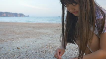 Little Asian child picking shells on the beach