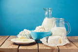 Dairy products on wooden table over blue background