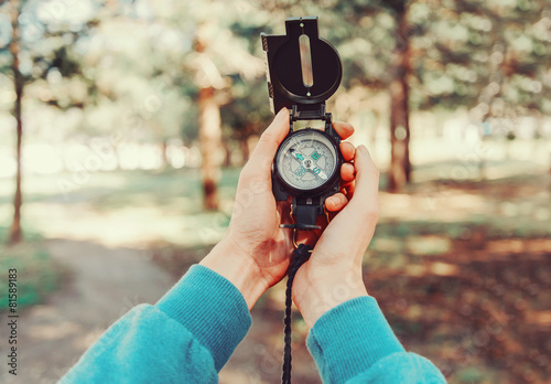 Traveler holding a compass  in summer forest - 81589183