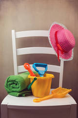 White chair with childs play items for day at the beach