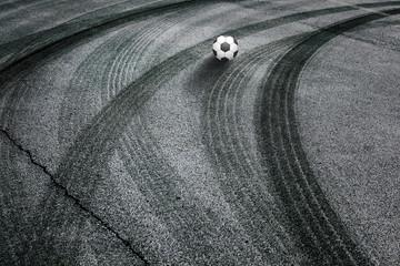 Abstract asphalt tires tracks with soccer ball